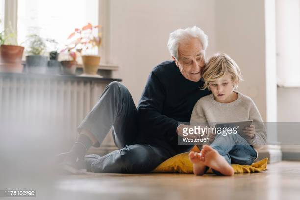 grandfather and grandson sitting on the floor at home using a tablet - hommes seniors photos et images de collection