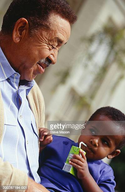 grandfather and grandson sitting outdoors, low angle view - drinks carton stock pictures, royalty-free photos & images