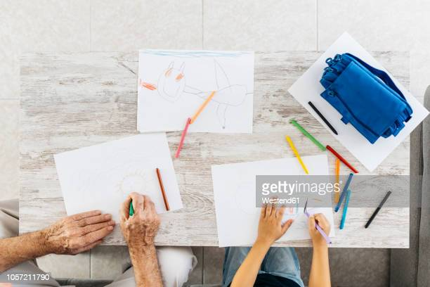 grandfather and grandson sitting side by side on the couch drawing with coloured pencils, top view - fianco a fianco foto e immagini stock