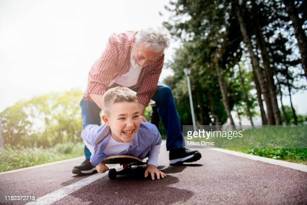 grandfather and grandson skateboarding together - caneleira roupa desportiva de proteção imagens e fotografias de stock
