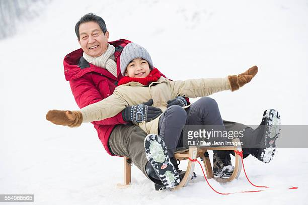 Grandfather and grandson sliding on a sled
