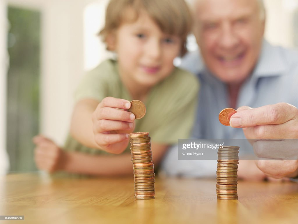 Grandfather and grandson stacking coins : Stock Photo