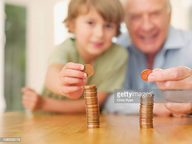 grandfather and grandson stacking coins - penny for the guy stock photos and pictures