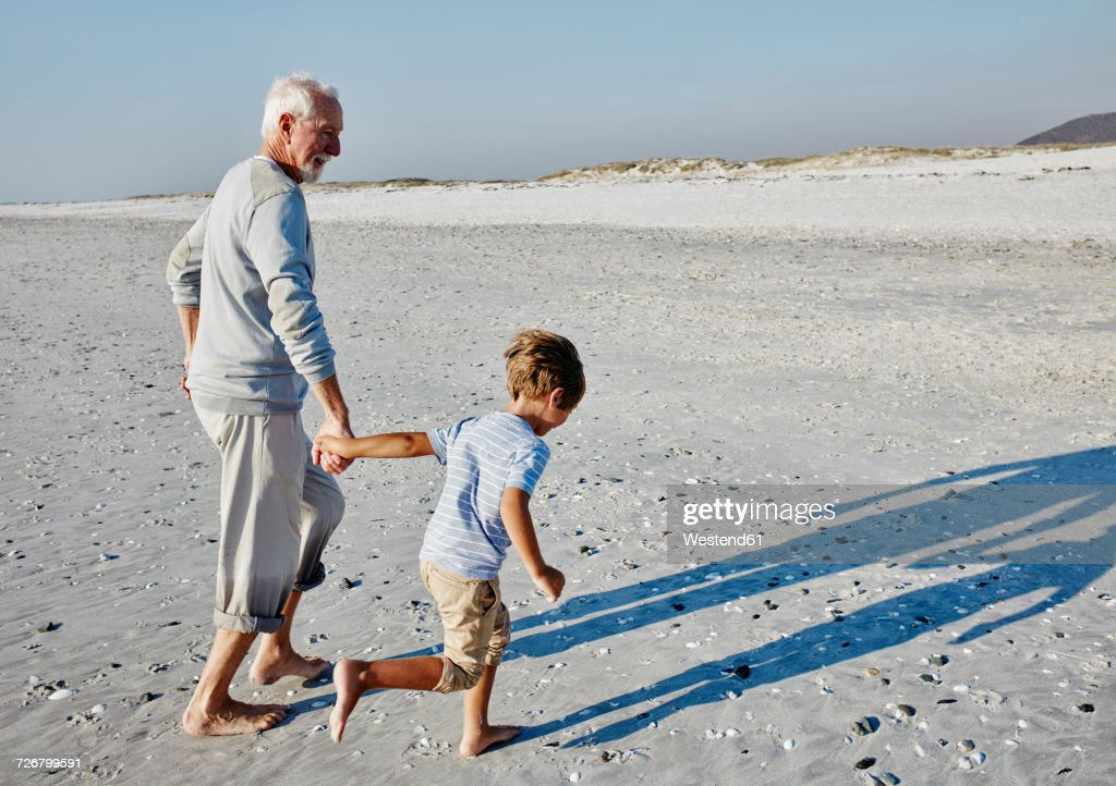 Grandfather and grandson strolling on the beach : Stock Photo