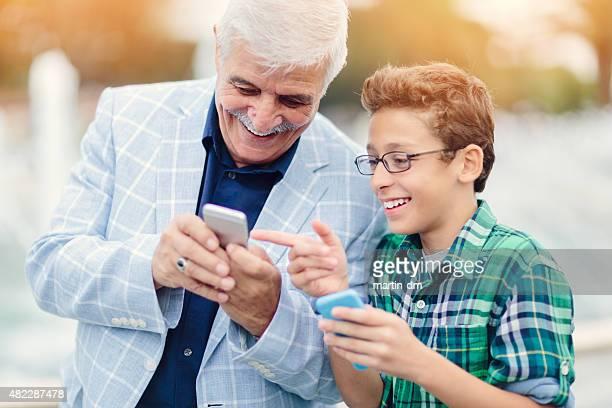 Großvater und Enkel beim Surfen im Internet auf smartphones