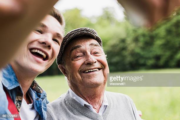 Grandfather and grandson taking selfie with smartphone