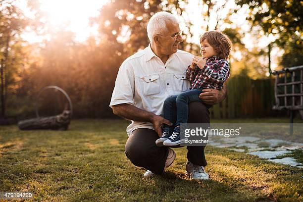 Großvater und Enkel sprechen mit einander bei Sonnenuntergang.