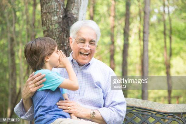 Grandfather and grandson tell secrets outdoors together.