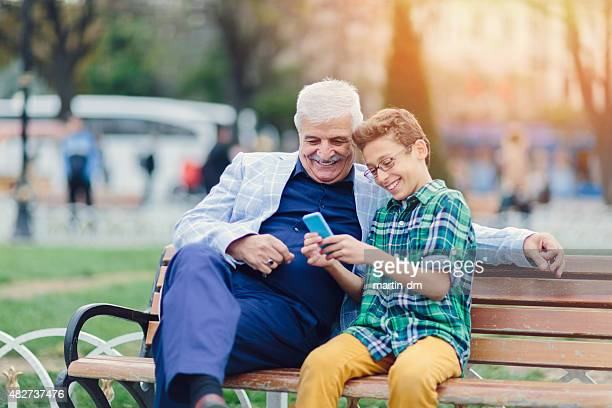 Grandfather and grandson texting on smartphone