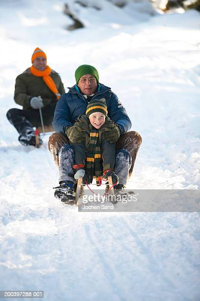 Grandfather and grandson (8-10) tobogganing in snow, smiling