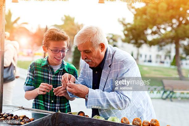 Grandfather and grandson trying chestnuts in Istanbul.