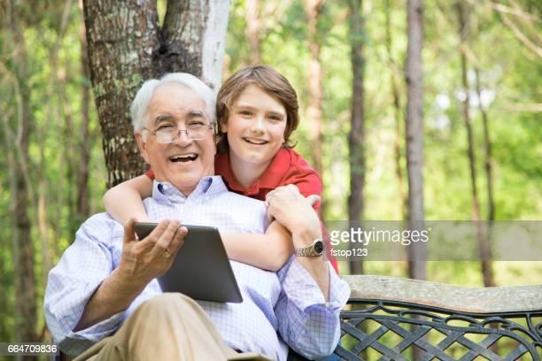 Großvater und Enkel, die mit digitalen Tablet im freien zusammen.