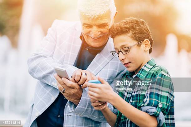 Grandfather and grandson using smartphones in the city park