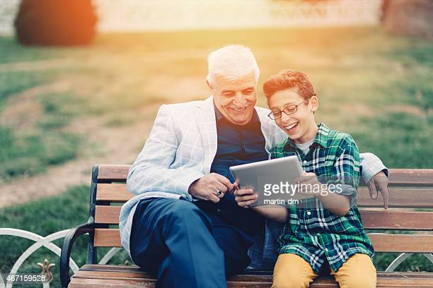 Grandfather and grandson using tablet in the city park