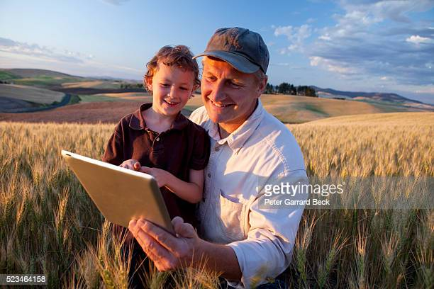 Grandfather and grandson (4-5) using tablet pc in wheat field