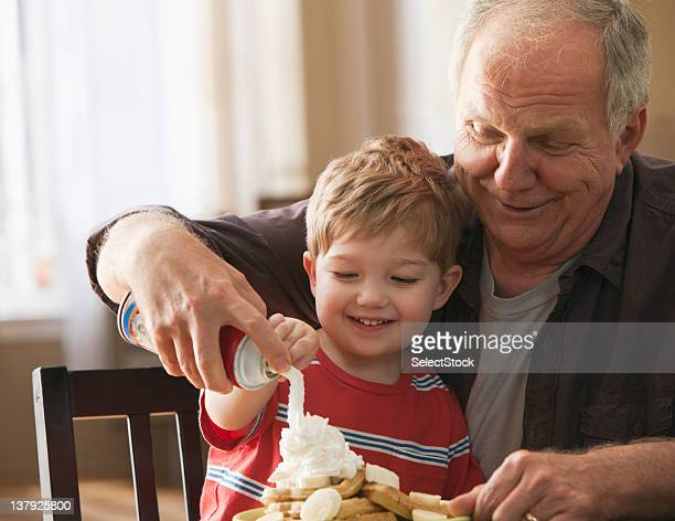 Grandfather and grandson using whipped cream on waffles