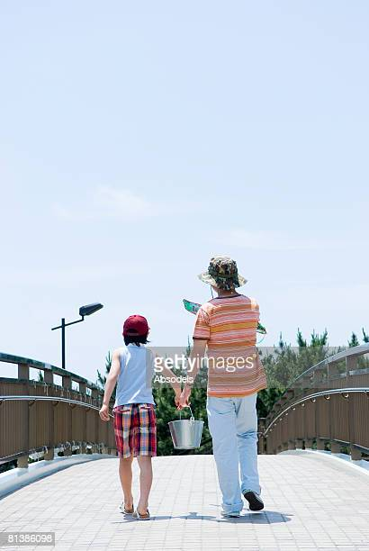 Grandfather and grandson (8-9) walking on bridge, rear view