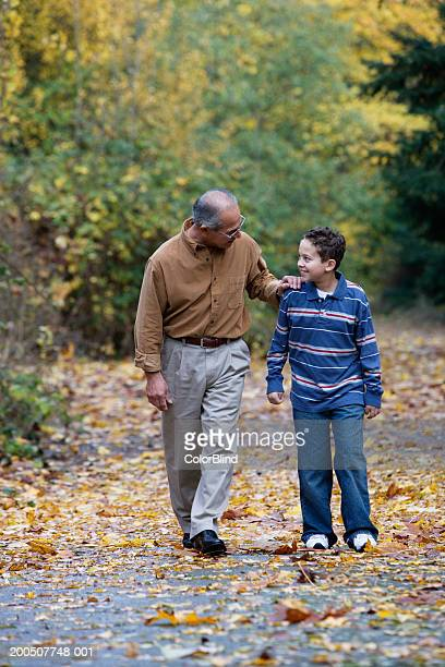 Grandfather and grandson (9-11) walking on path, autumn