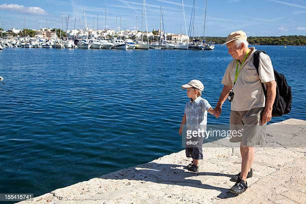 Grandfather And Grandson Walking On Waterfront in Harbour