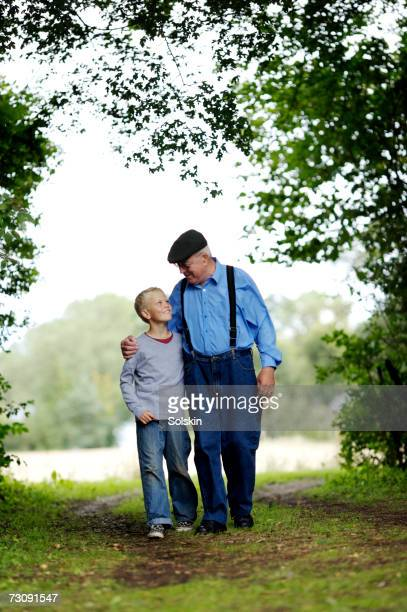 Grandfather and grandson (10-11) walking together, arms around each other