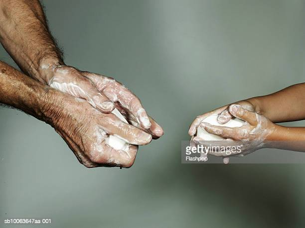grandfather and grandson (6-7) washing hands with bar of soap, close-up - handwashing stock pictures, royalty-free photos & images