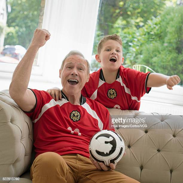 grandfather and grandson (10-12 years) watching sports event - 55 59 years stock pictures, royalty-free photos & images
