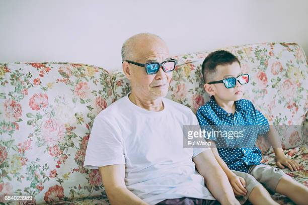 Grandfather and grandson watching with 3D glasses