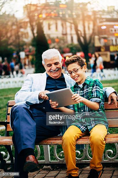 Grandfather And Grandson With Digital Tablet