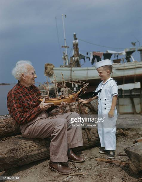 grandfather and grandson with model ship on beach  - uniform cap stock pictures, royalty-free photos & images