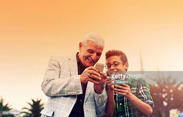 Grandfather And Grandson with phones