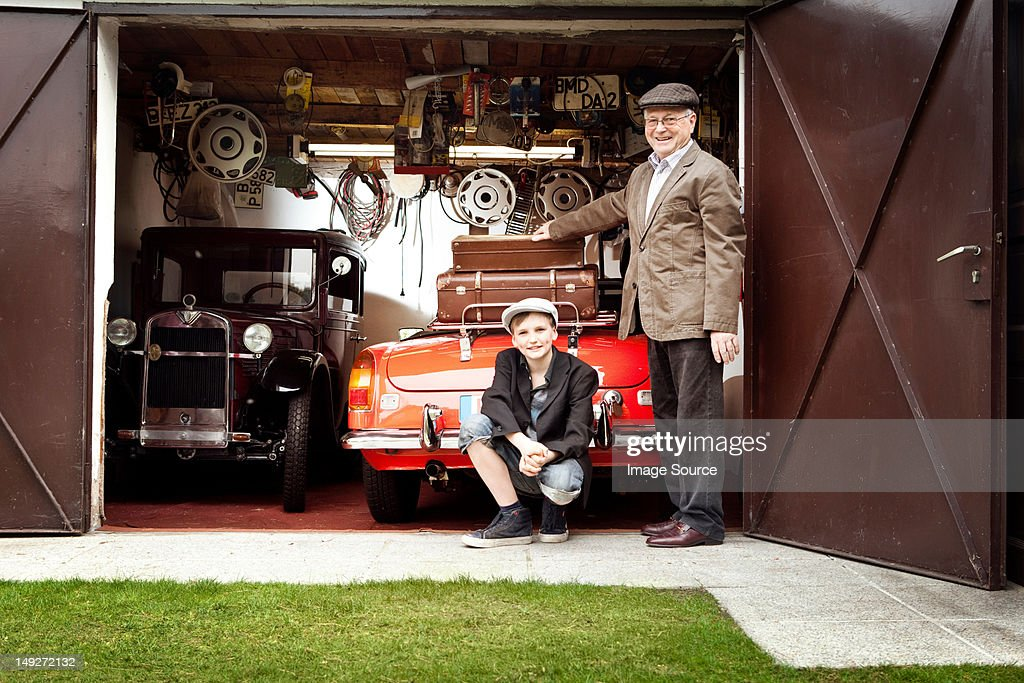 Grandfather and grandson with vintage car and trunk suitcases in garage : Stock Photo