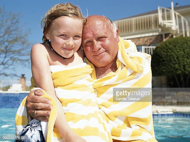 grandfather and grandson wrapped in towel by swimming pool, portrait - wrapped in a towel stock pictures, royalty-free photos & images