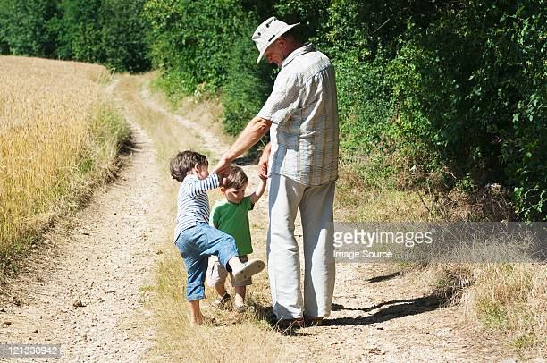 Grandfather and grandsons walking on rural road