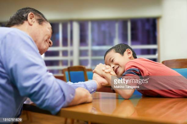 grandfather and his grandson are arm-wrestling - effort stock pictures, royalty-free photos & images