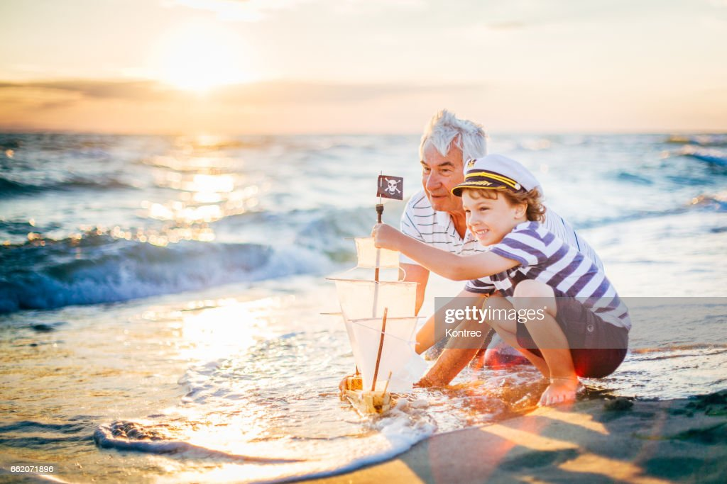 Grandfather and his grandson having fun on a beach : Stock Photo