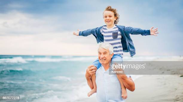 Grandfather and his grandson having fun on the beach