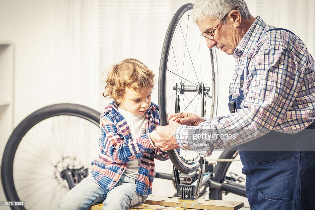 Grandfather and his grandson repairing a bicycle : Stock Photo