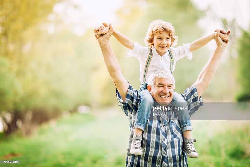 Grandfather and his grandson walking outdoors : Stock Photo