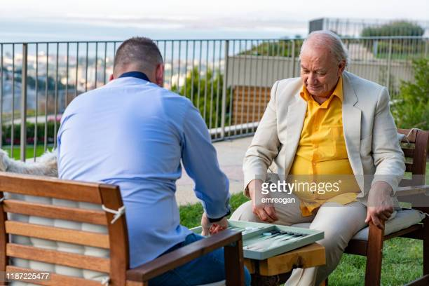 grandfather and his son are playing backgammon in the garden - backgammon stock pictures, royalty-free photos & images