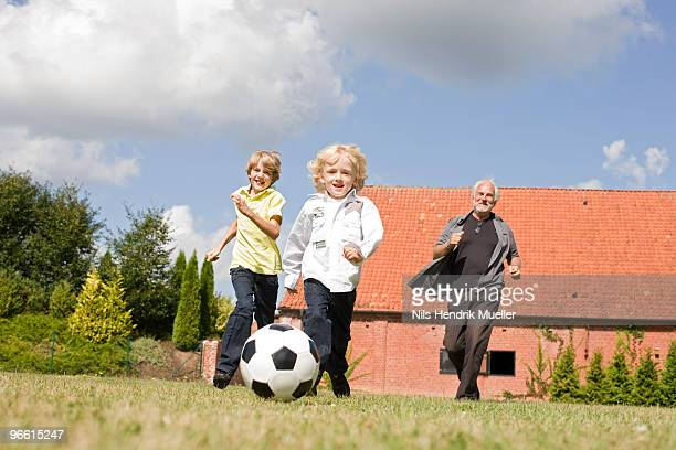 grandfather and kids playing football