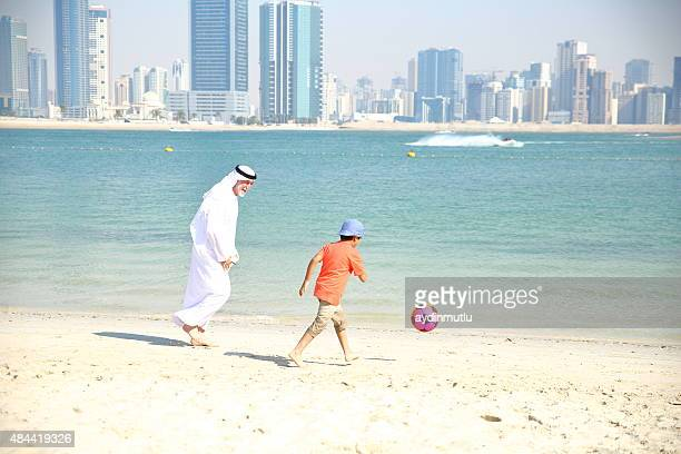 Grandfather and little boy playing ball  on the beach.