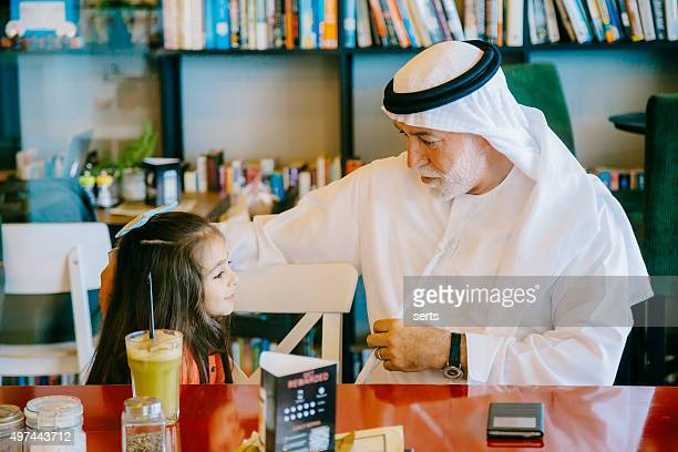Grandfather and little girl having fun at cafe