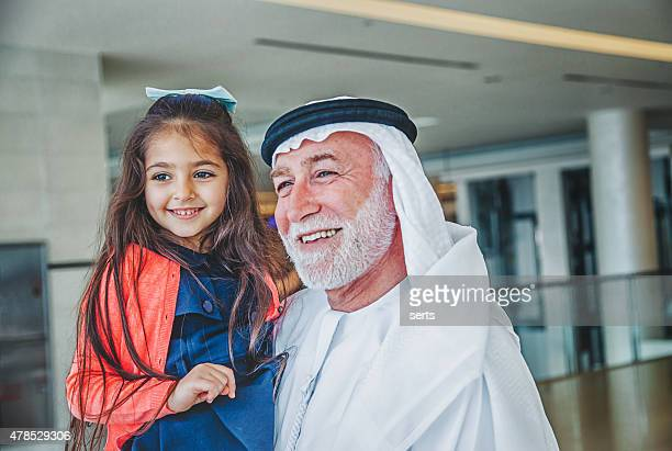 Grandfather and little girl having fun at shopping mall