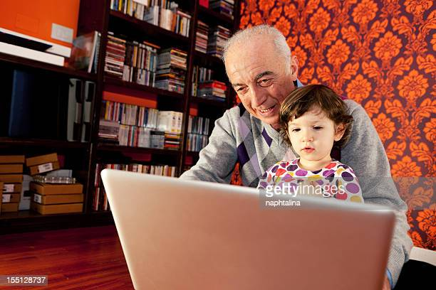grandfather and niece at computer - niece stock photos and pictures