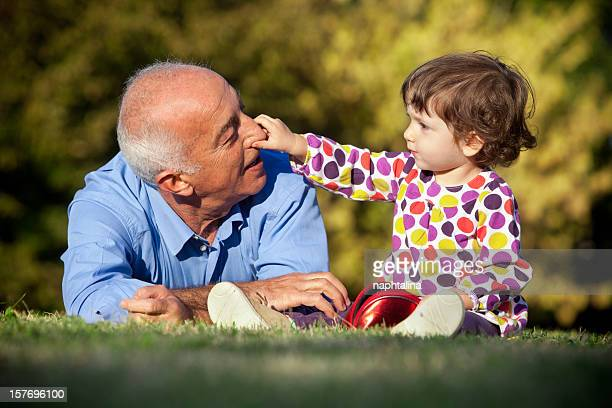 a grandfather and young granddaughter bonding at the park - niece stock pictures, royalty-free photos & images