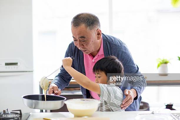 Grandfather and young grandson making pancakes together
