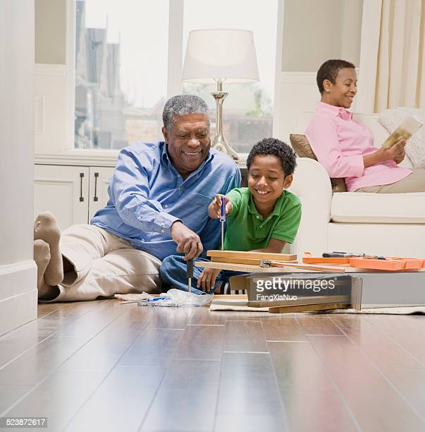 Grandfather Assembling Furniture With Grandson