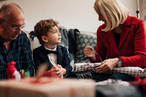 Grandfather assisting children in untying Christmas presents while sitting in living room - gettyimageskorea