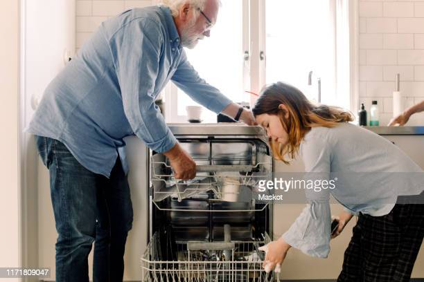grandfather assisting granddaughter in cleaning dishwasher at kitchen - generation gap stock pictures, royalty-free photos & images