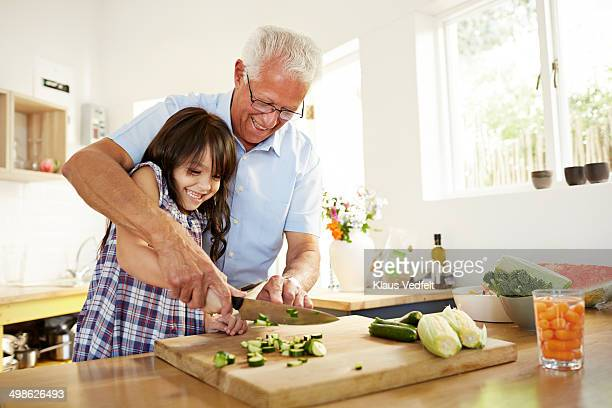 Grandfather assisting granddaughter with chopping